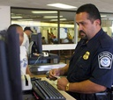 A Customs and Border Protection officer enters a passenger's information at Dulles International Airport.