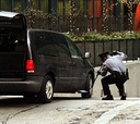 A security guard checks underneath a vehicle entering a federal complex in Chicago.