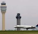 A plane lands near an air traffic control tower at Hartsfield-Jackson Atlanta International Airport.