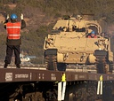 A Korean contractor directs the driver of a U.S. Army vehicle during an exercise.