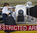 A TSA officer scans bags at Dulles International Airport.