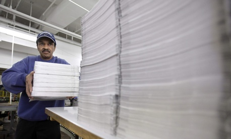 Clark Hopkins loads piles of the appendix of the fiscal 2012 federal budget at the Government Prinding Office.