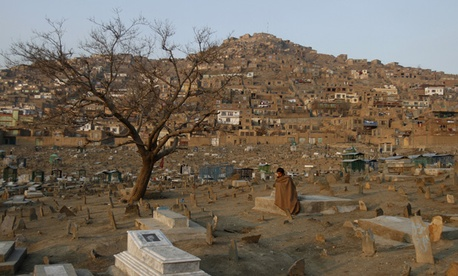 A man sits in a cemetery in Kabul in January.