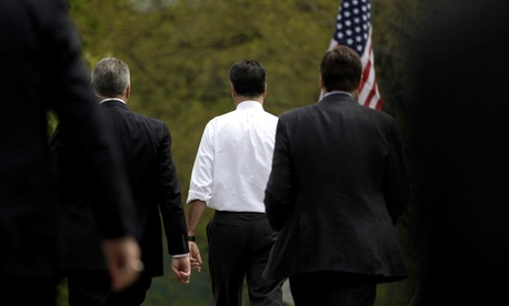 Mitt Romney walks with Secret Service agents.