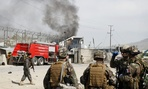 NATO soldiers watch smoke billow after a Talban attack Wednesday in Kabul.