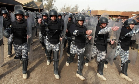 Iraqi police march during a graduation ceremony.