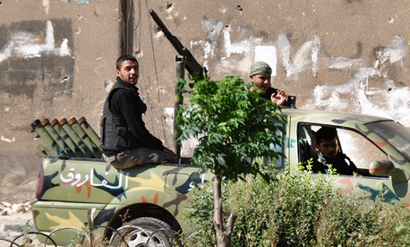 Syrian rebels patrol Khaldiyeh neighborhood, in Homs province.