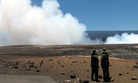 Two park rangers look out at Hawaii Volcanoes National Park.
