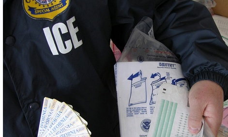  An ICE officer holds fake test scores and ID cards after a bust on a fake student visa ring in 2010.