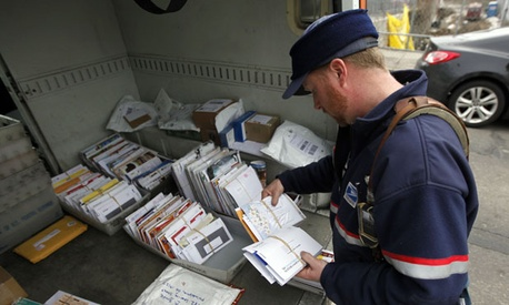 A Philadelphia postal worker sorts mail in his truck.