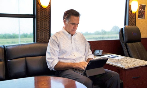 Mitt Romney works on an iPad while campaigning.
