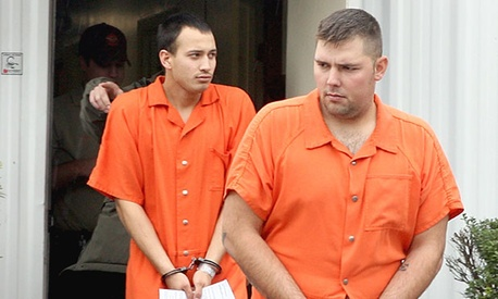 U.S. Army Sgt. Anthony Peden, 25, right, and Pvt. Isaac Aguigui, 19 are led away in handcuffs after appearing before a magistrate judge in December.