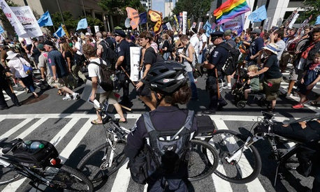 Police observe protestors Monday in Charlotte.