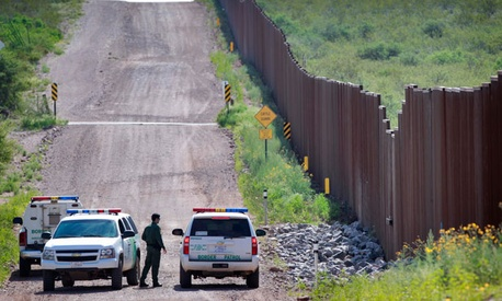 Agents confer near the border in Naco, Ariz.