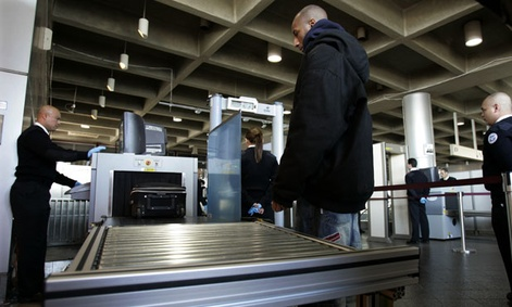 A  Homeland Security screener looks at an X-ray scan of a suitcase of a train passenger in 2006.