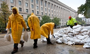 Workers haul sandbags in front of the Justice Department.