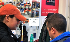 D.C. residents purchase last minute supplies, including a dwindling supply of sadbags, from Ace Hardware on Monday afternoon.
