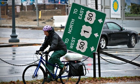 A cyclist rides by a downed traffic sign and the Smithsonian National Museum of African American History and Culture in Washington Tuesday after the storm.