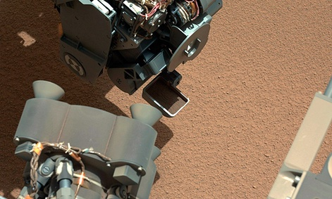 The Curiosity Rover uses it&#39;s robotic arm to scoop sand.