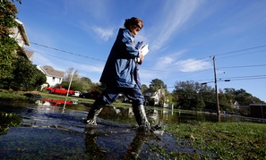 Letter carrier Dawn Greco wades in the water to deliver the mail after superstorm Sandy.