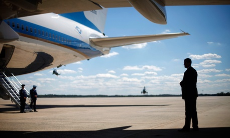 A Secret Service agent stands at right underneath the wing of Air Force One.