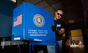 A worker brings voting equipment into East Elementary School in Long Beach, N.Y., Monday Nov. 5, 2012, as it is set up to serve as a polling station for election day Tuesday.