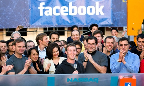 Facebook founder, Chairman and CEO Mark Zuckerberg, center, rings the opening bell of the Nasdaq stock market after his company priced its IPO.