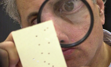A Florida election worker inspects a ballot in 2000.