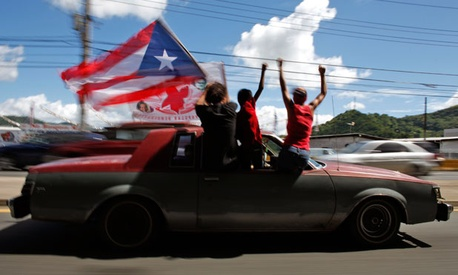 People ride atop a vehicle waving a Puerto Rican flag during elections in San Juan, Puerto Rico, Tuesday, Nov. 6, 2012.