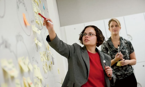 OPM's Sarah Hassmer (left) and Cassie Cunfer facilitate a stakeholder mapping exercise in problem solving.