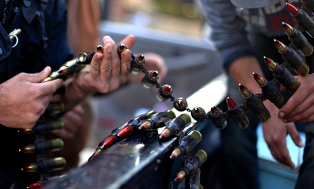 Syrian fighters check their ammunition during clashes with Syrian army forces in the town of Harem.