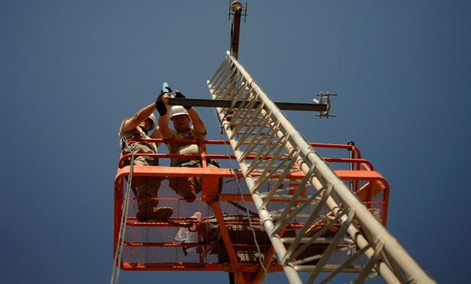 An Army technician attaches a high frequency radio antenna to a communications tower in 2008.