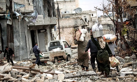 Syrian residents carry their belongings after their homes were damaged due to fighting between Free Syrian Army fighters and government forces in Aleppo. 