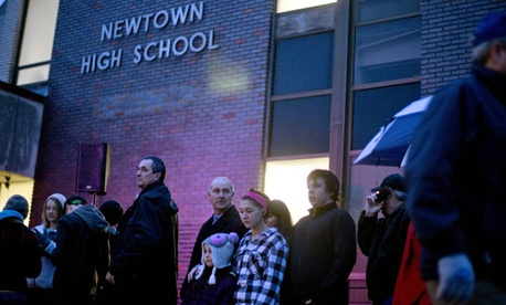 People wait in line to attend a memorial at Newtown High School Sunday.