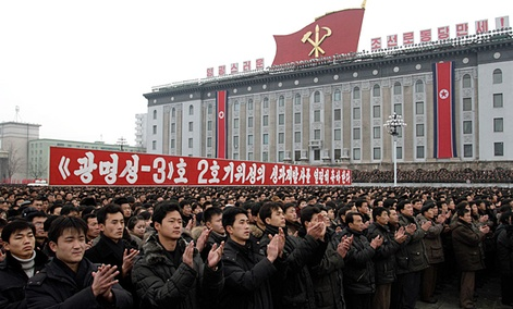 North Koreans applaud near a slogan which reads (we) fervently celebrate the successful launch of the second version of the Kwangmyongsong-3 satellite 2nd version&#34; during a mass rally in Pyongyang.