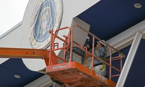 A painter works on the presidential viewing stand outside the White House in preparation for the inauguration.