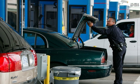 U.S. Customs and Border Patrol officer Jefferey Hill checks the trunk of a motorist's vehicle entering the United States at the border crossing in Buffalo, N.Y.