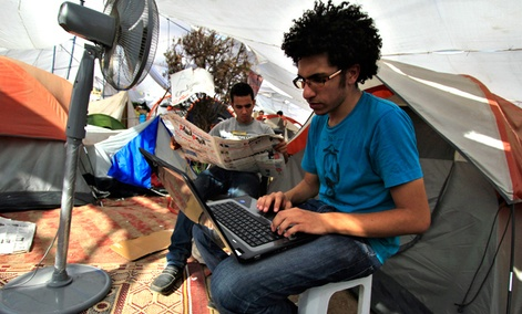 An Egyptian protester uses his laptop next to a cooling fan in Cairo&#39;s Tahrir Square in July 2011. 