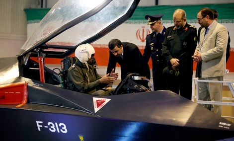 Iranian President Mahmoud Ahmadinejad, center, listens to an unidentified pilot during a ceremony to unveil Iran&#39;s newest fighter jet, Qaher-313.