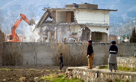A police commando stands guard as authorities use heavy machinery to demolish Osama bin Laden's compound in Abbottabad, Pakistan.