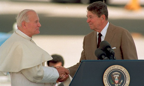 U.S. President Ronald Reagan shakes hands with Pope John Paul II on the podium at Miami International Airport, Fla., on Sept. 10, 1987.