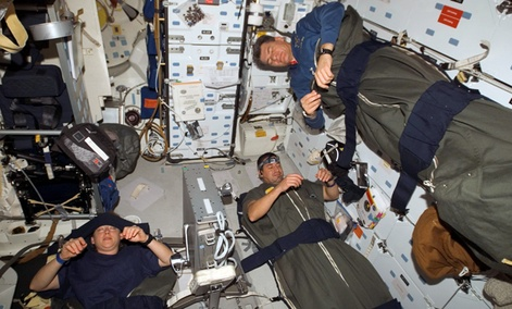 Astronauts Pam Melroy, George Zamka, bottom right,and European Space Agency&#39;s Paolo Nespoli, sleep in their sleeping bags, which are secured on the middeck of the Space Shuttle Discovery while docked with the International Space Station.