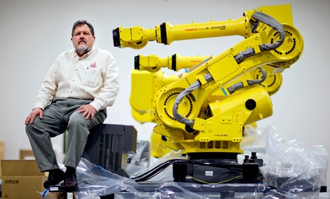 Rosser Pryor, Co-owner and President of Factory Automation Systems, sits next to a new high-performance industrial robot at the company's Atlanta facility.