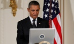 President Barack Obama uses a laptop computer to send a tweet during a &#34;Twitter Town Hall.&#34;