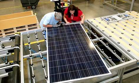 Stacey Rassas, right, a quality control manager at a Suntech Power Holdings Co., a Chinese-owned solar panel manufacturer, examines a solar panel.