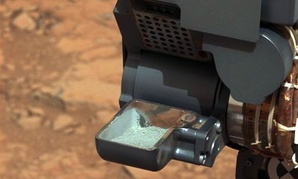 The Curiosity rover holding a scoop of powdered rock on Mars. The rover recently drilled into a Martian rock for the first time and transferred a pinch of powder to its instruments to analyze the chemical makeup.
