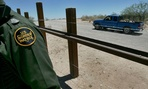 A Customs and Border Protection agent walks next to the Mexico border in Arizona.