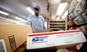Packages wait to be sorted in a Post Office as U.S. Postal Service letter carrier of 19 years, Michael McDonald, gathers mail to load into his truck before making his delivery run.