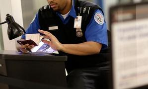 A TSA agent checks a passport at Baltimore Washington Airport.