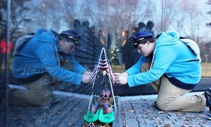 Bruce Wolff, 14, of Canton, Ohio, kneels for a closer look at items left at the Vietnam Veterans Memorial wall. More than 400,000 items have been left since the wall opened in 1982.
